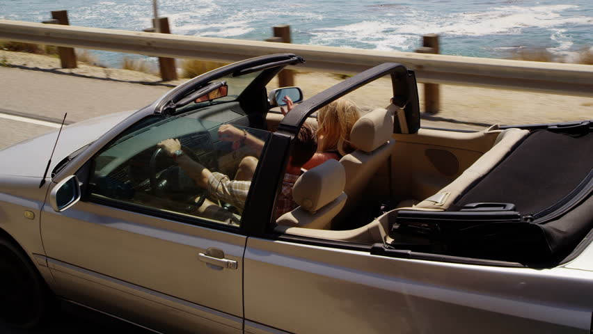 Couple driving convertible together along beach - HD stock video clip