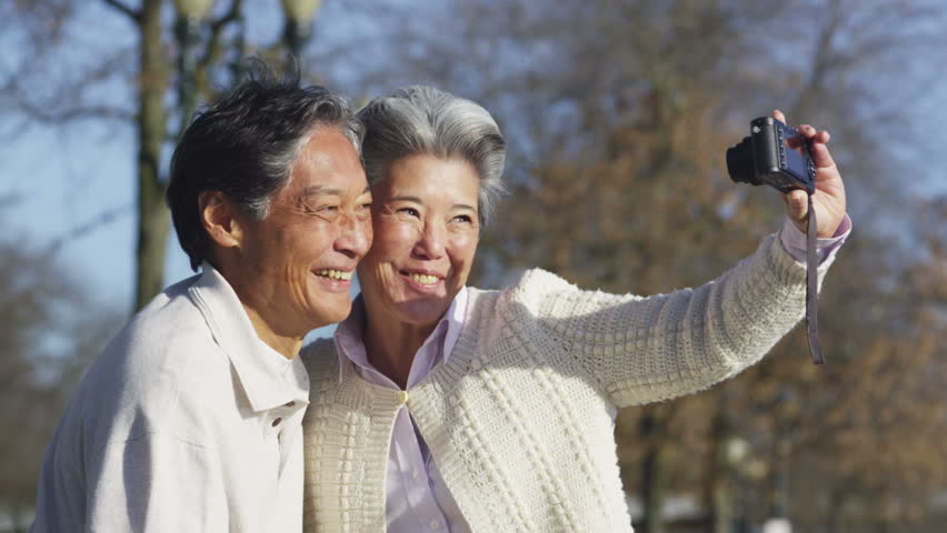 Senior couple with camera taking photo together