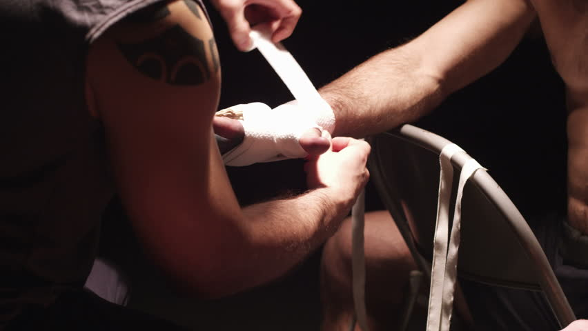 Close up of a fighter getting his hands wrapped by a trainer in a dark room - HD stock footage clip