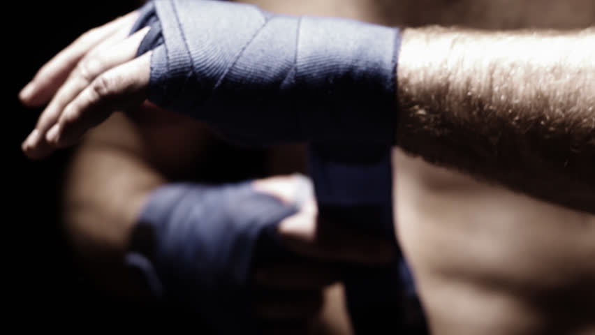 Mixed martial arts athlete wraps his hand with blue cloth. Close up shot. - HD stock video clip