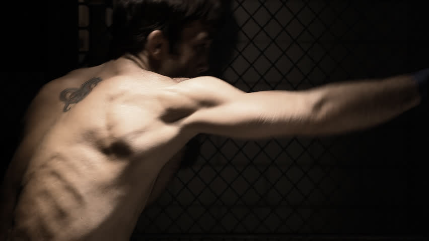 Profile of a mixed martial arts athlete shadow boxing. Medium shot. - HD stock video clip
