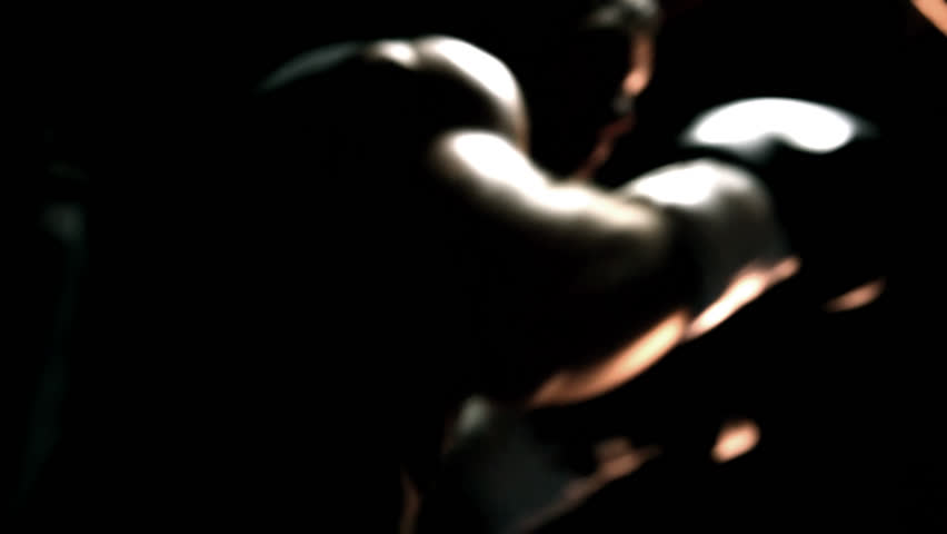 Muscular athlete practices boxing on a punching bag. Close up shot. - HD stock footage clip