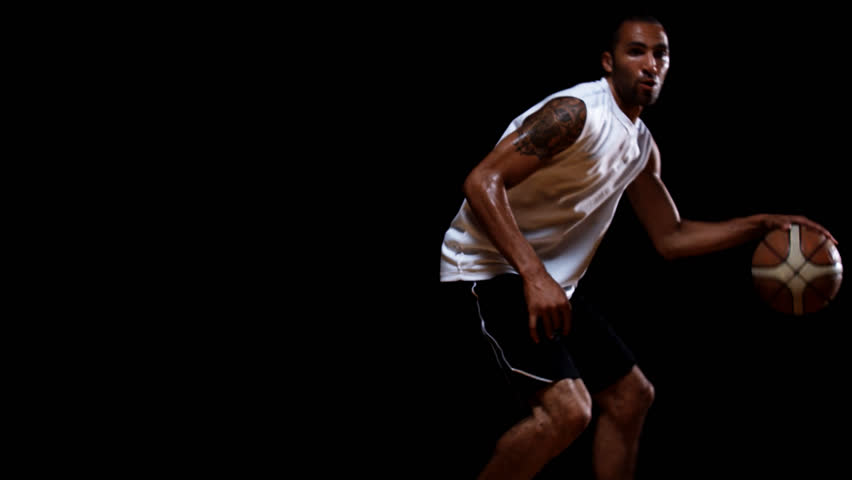 An isolated basketball player lit in a dark room, dribbles and handles the ball as he runs and spins towards the camera in slow motion