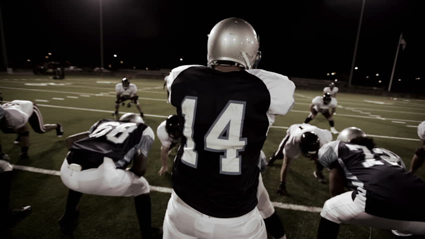 Over the shoulder view of a quarterback in the huddle and walking to the line before the snap - HD stock footage clip