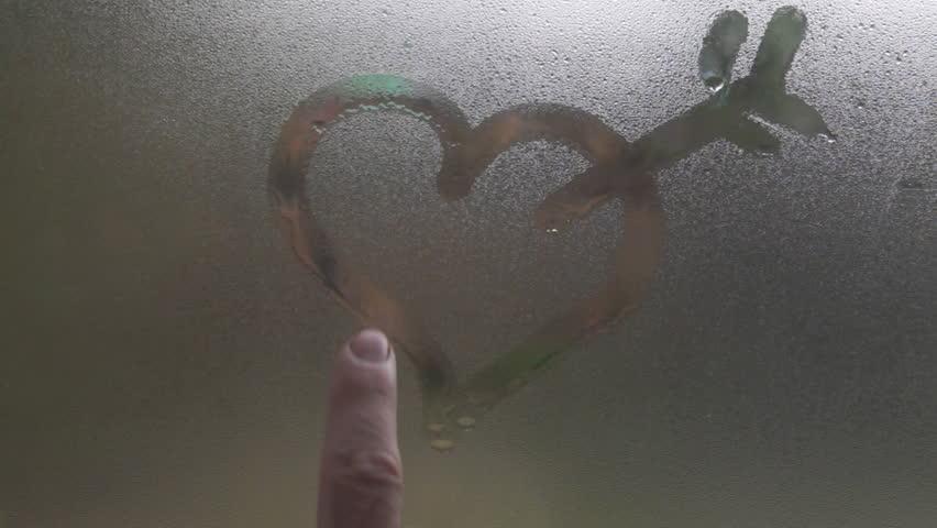 Man draws a heart with an arrow on misted window - HD stock footage clip