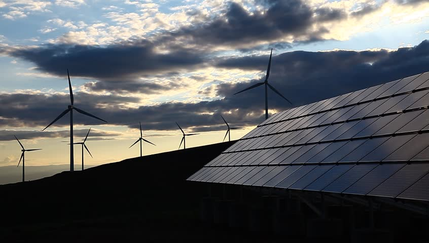 wind turbines and solar panels silhouetted at sunset.