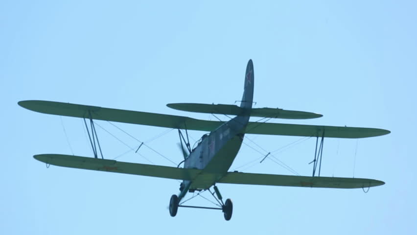 Green biplane ascending to the sky at the Mochishe airshow, Novosibirsk.