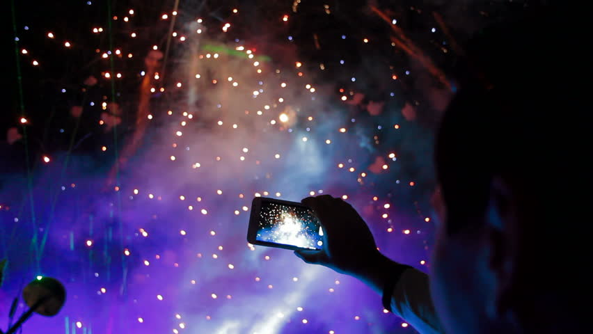 Man filming colorful fireworks on his cell phone.