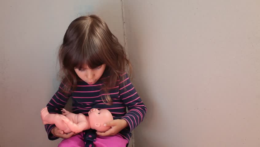 Little baby girl holds, hugs and takes care of doll puppet. Childhood idea and concept. Medium indoor/interior shot. Natural daylight.  - HD stock video clip