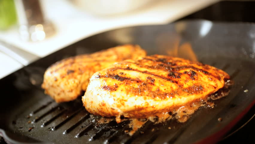 Tasty free range chicken breasts grilling and being charred on a hot griddle pan for a healthy balanced meal