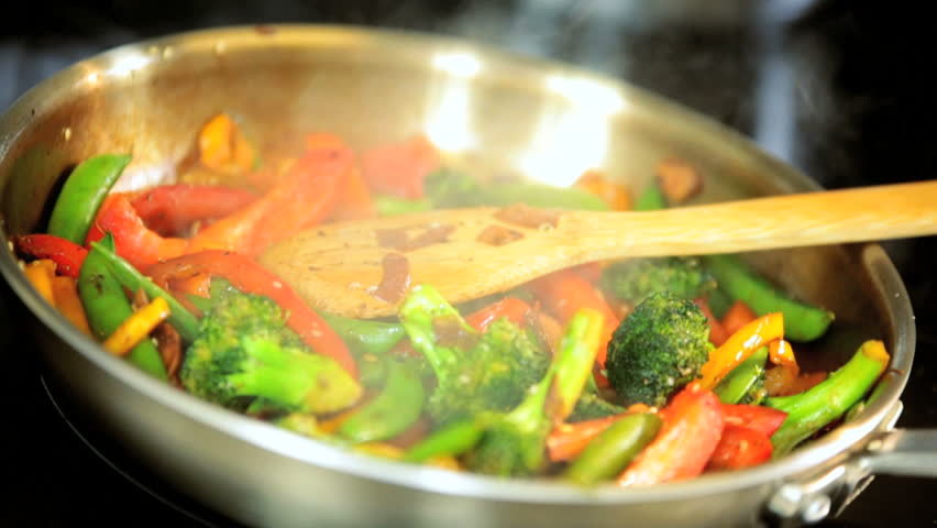 Tasty Asian pan fry close up with fresh peppers, broccoli, and mushrooms being stir fried for a healthy vegetarian meal - HD stock footage clip