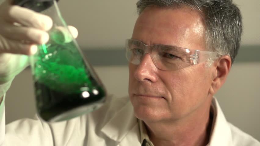 Scientist shaking green fluid in beaker - HD stock video clip