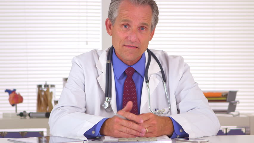 Sincere doctor talking and looking at camera