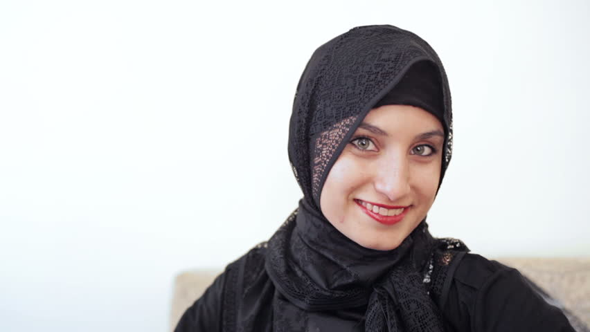 headshot of young millenial teenage muslim girl with grey eyes a hijab headscarf and red lipstick smiling