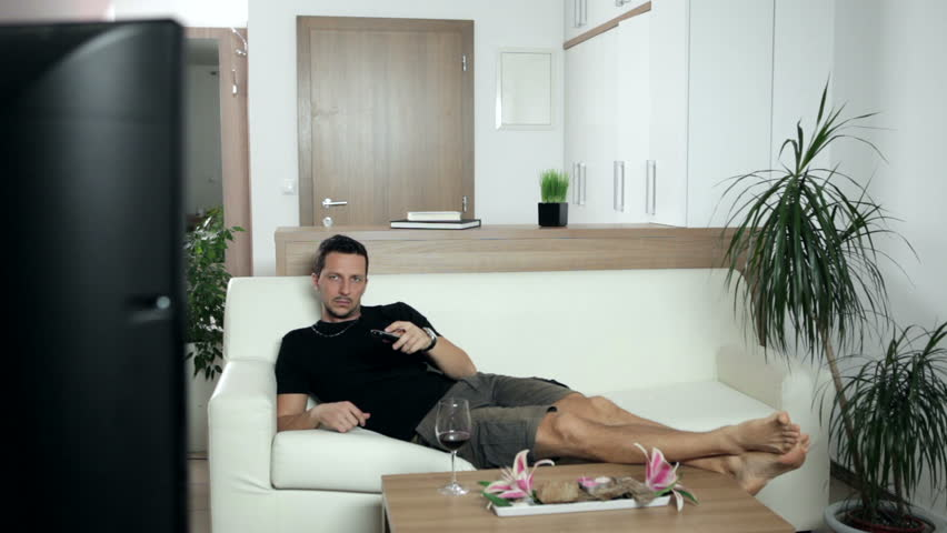 Woman cleaning a house while man is watching TV. Wide shot. High definition video. - HD stock video clip