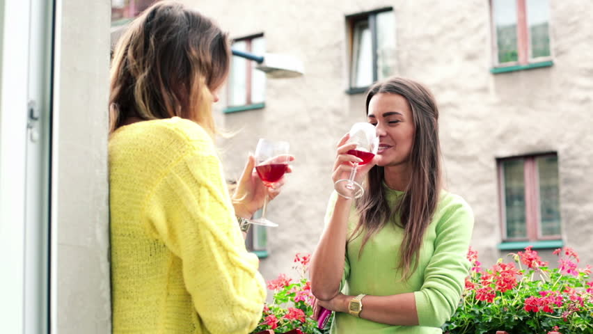 Two young girlfriends drinking wine on balcony  - HD stock video clip