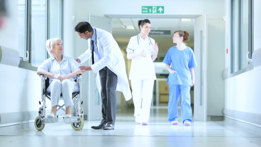 Multi-ethnic medical staff talking about patient care in busy hospital hallway and moving patient in wheelchair | Shutterstock HD Video #4820969
