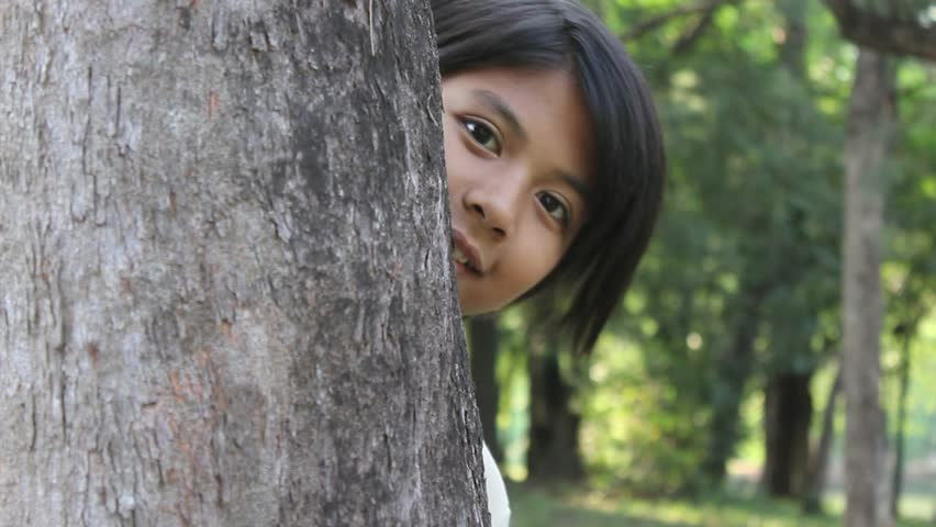 Hide and Seek: young girl playing in the park - HD stock video clip