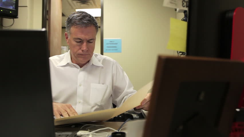View from between objects in the foreground to a businessman busy working at his desk on paperwork. - HD stock footage clip