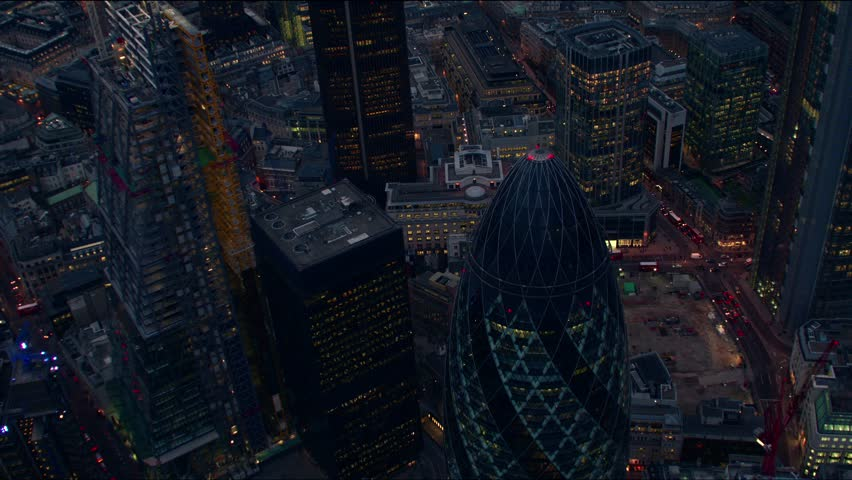 Dramatic evening aerial sequence of The City of London financial district, flying over the Gherkin building (30 St Mary Axe) and the Tower 42 building.