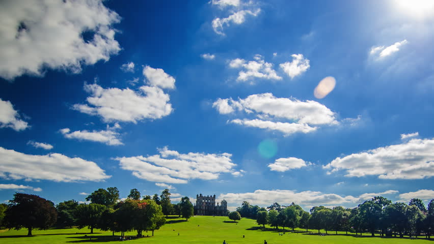 Old mansion in the park, sunny sunday with blue sky and fluffy clouds in a time lapse - HD stock video clip