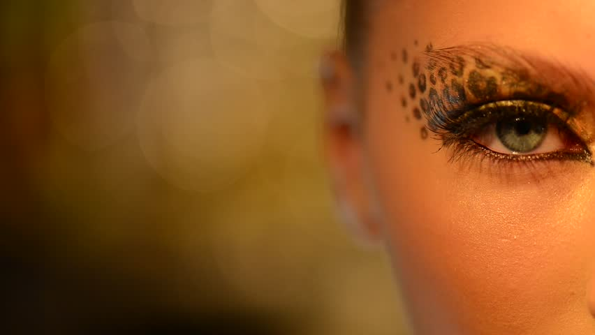 Beauty Fashion Model Girl with Holiday Leopard Makeup. Golden Wild Cat Eyes Make-up Eyeshadow. Beautiful Woman Face over golden blurred Background. Animal Make up - HD stock footage clip