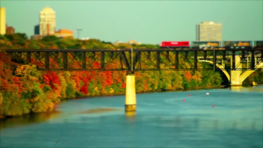 A tilt shift shot of a freight train crossing the Mississippi river from Saint Paul into Minneapolis on a sunny autumn day. - HD stock video clip