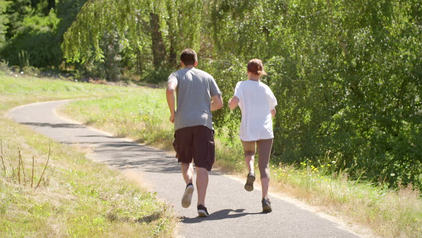 Fit and healthy young couple run through the park - HD stock video clip