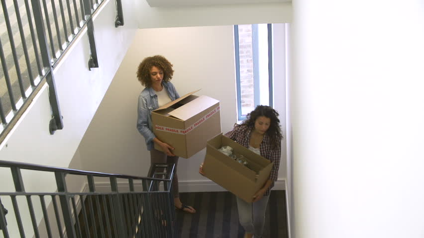 Two young women carrying boxes up to their new apartment together