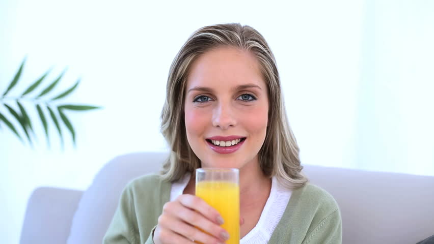 Beautiful woman drinking a glass of orange juice on couch - HD stock video clip