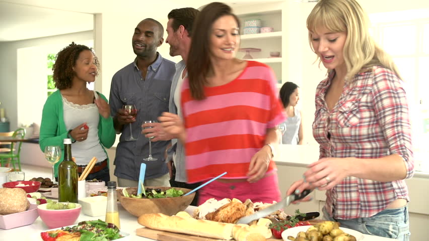 Group of friends eating, talking, and drinking in kitchen before a delicious buffet at a dinner party #4879721