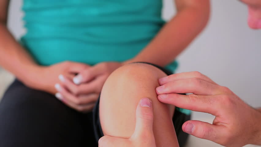 Physiotherapist checking his patients knee in his office