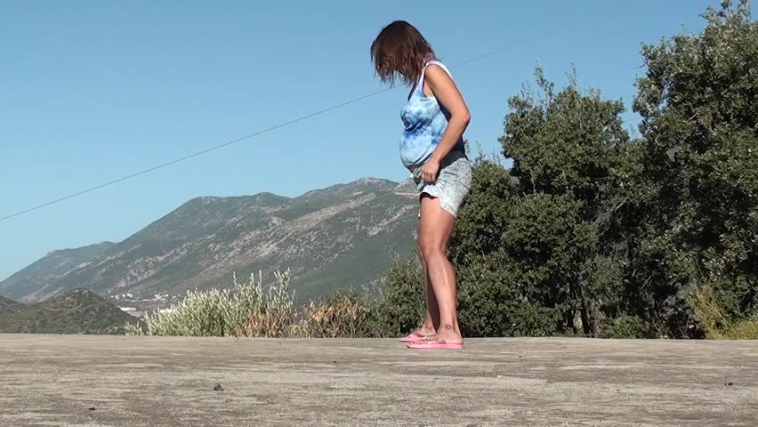 A pregnant woman does gym outdoors  leg-split with bends back and forward, sidewise - HD stock video clip