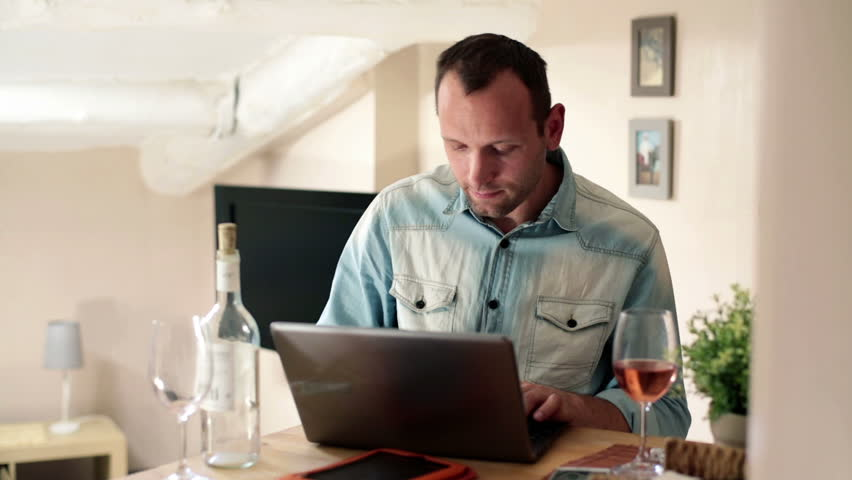 Young man working on laptop and drinking wine at home  - HD stock footage clip