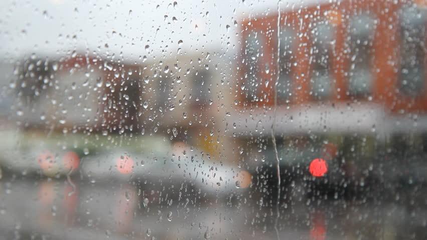 Rainy city. View of rainy street. Man with rain jacket walks by. Shallow depth of field. Bloor St, Toronto, Ontario, Canada.