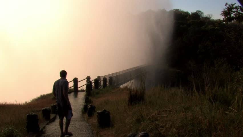 ZAMBIA - MAY 2009: Young tourist male walks across drenched bridge at the Victoria Falls, Zambia  - HD stock video clip