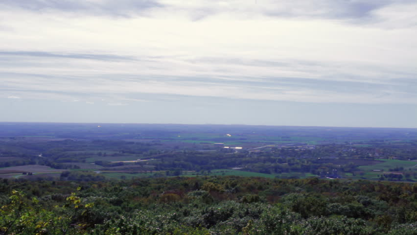 An expansive view of Wisconsin countryside in the Fall. Shot from the Blue Mounds State Park hill, clouds soar over treetops bright with fall colors, green fields, farmhouses and rural homesteads. - HD stock video clip