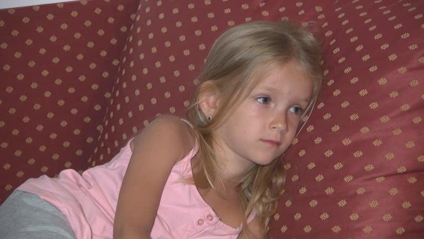 bored sad child watching tv sleepy little girl lying on