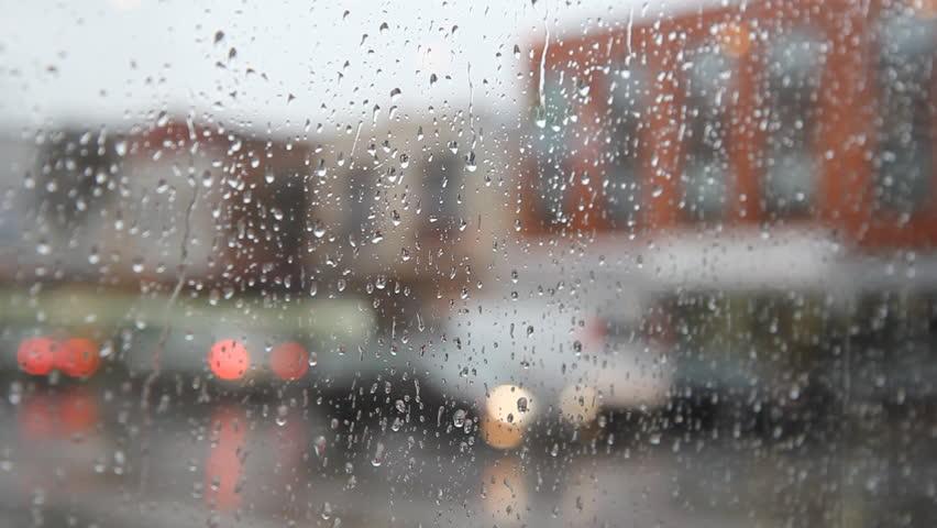 Rainy city. White umbrella woman. View of rainy street. Woman with white umbrella walks by.