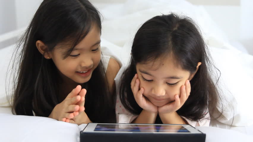 Little Asian girls play on tablet on the bed