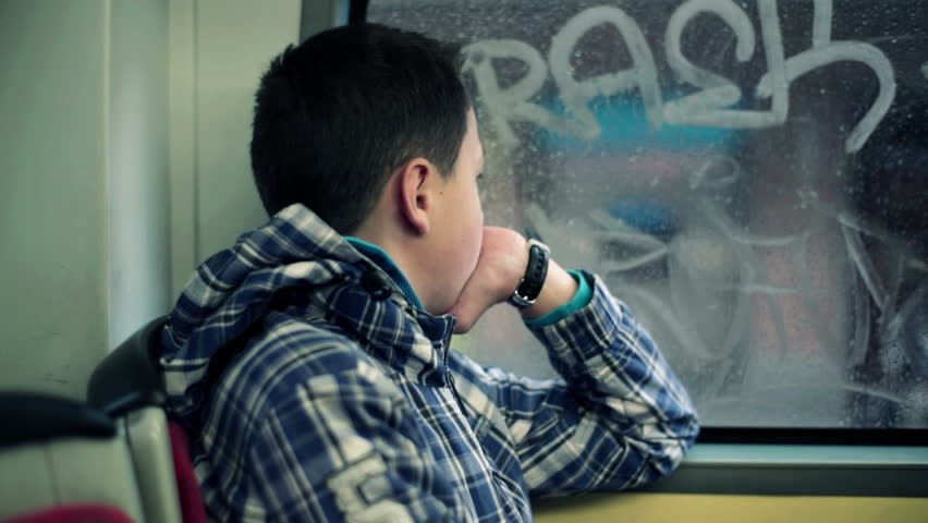 Young boy riding bus and looking out the window