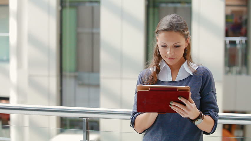 young, attractive business woman with tablet computer in office building. girl dressed in comfortable clothes, against the background of elevator rides. she looks very happy and successful
