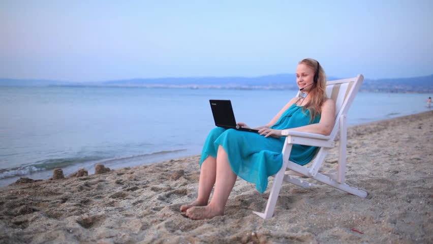 Woman relaxing at the beach in a deckchair alongside the ocean with her laptop computer and wearing a headset talking with her friend with skype - HD stock footage clip