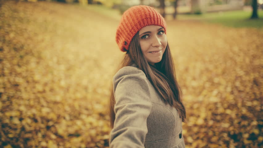 Young woman pulling her boyfriend through autumn park with leafs pov - HD stock video clip