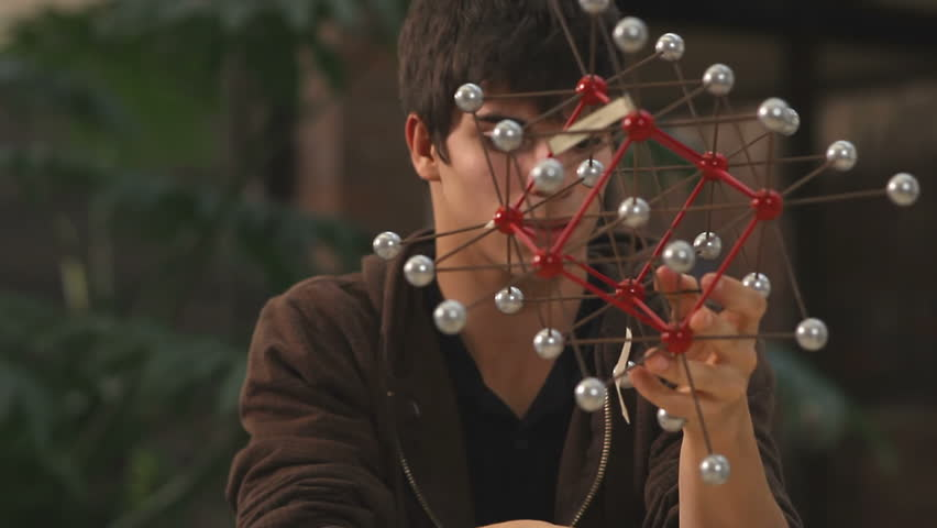 A student looks at a molecule model and takes notes while study - HD stock footage clip