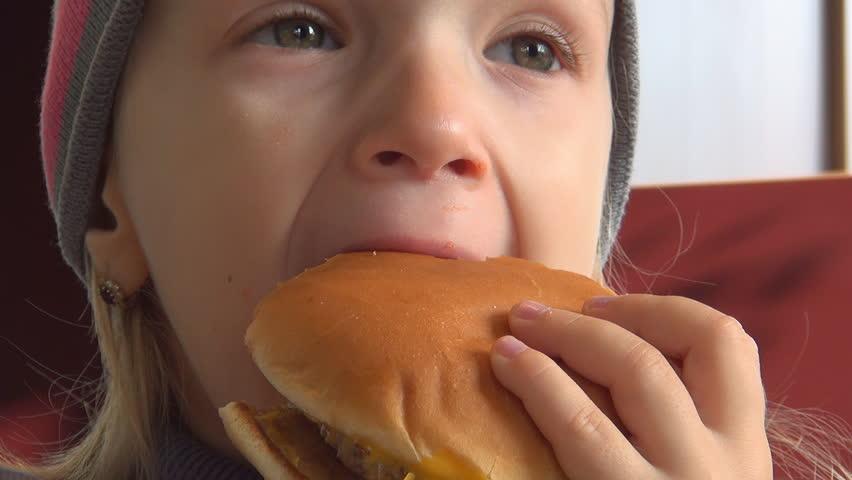 Child Eating Hamburger at Restaurant, Closeup of Hungry Girl Eating Fast Food - HD stock video clip
