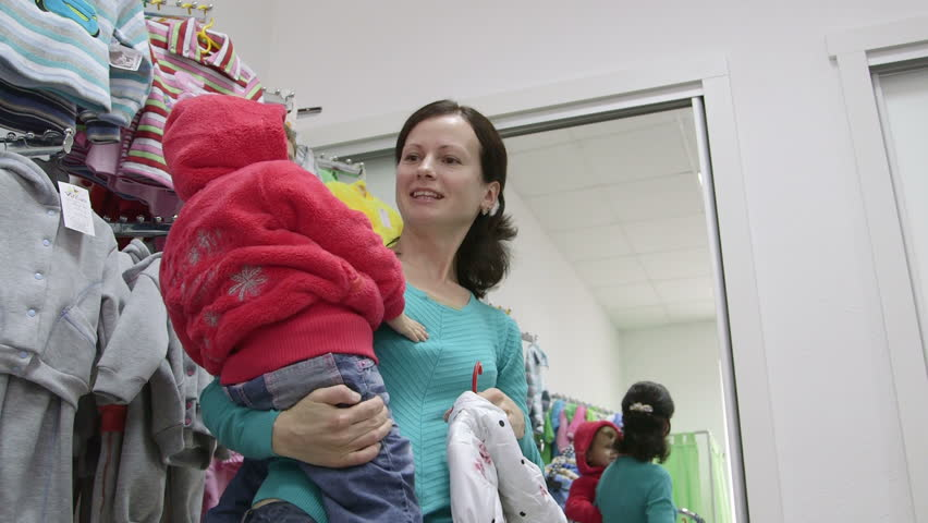 Happy mother with child in clothing store | Shutterstock HD Video #4998701