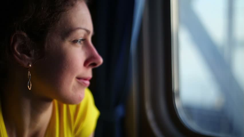 Flashes of sunlight on women face which watches in window of train during ride by bridge - HD stock video clip