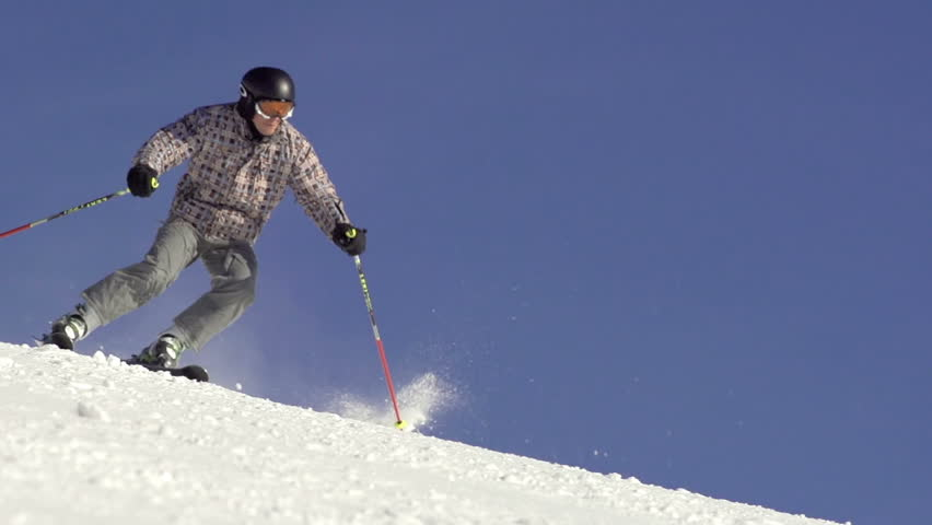 Slow Motion Of Skier Carving Down Fast And Snow Drifting. Focus Shifts.