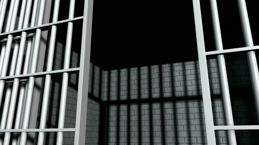 A static camera closeup of the door slamming shut a  brick jail cell with iron bars